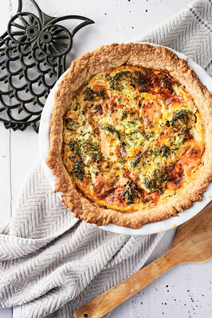 Overhead view of broccoli and smoked salmon quiche fresh out of the oven, on a grey hand towel, next to an owl trivet