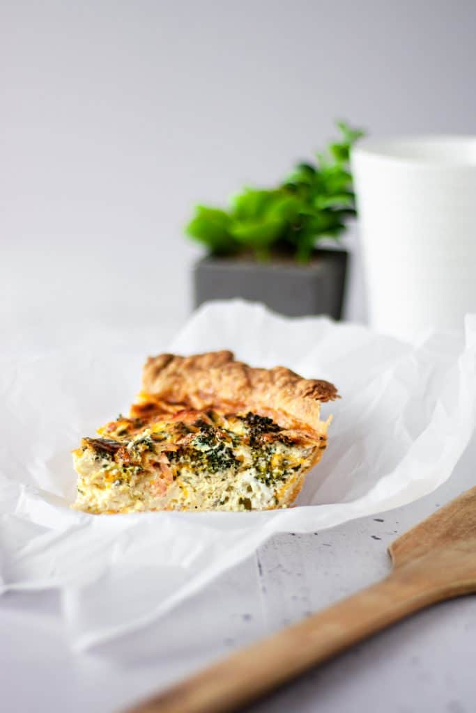 A slice of smoked salmon and broccoli quiche on parchment paper next to a wooden spoon with a coffee mug and plant in the background