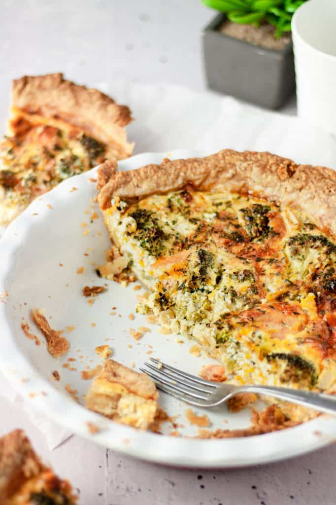A half eaten broccoli and a smoked salmon pie in a white pie dish
