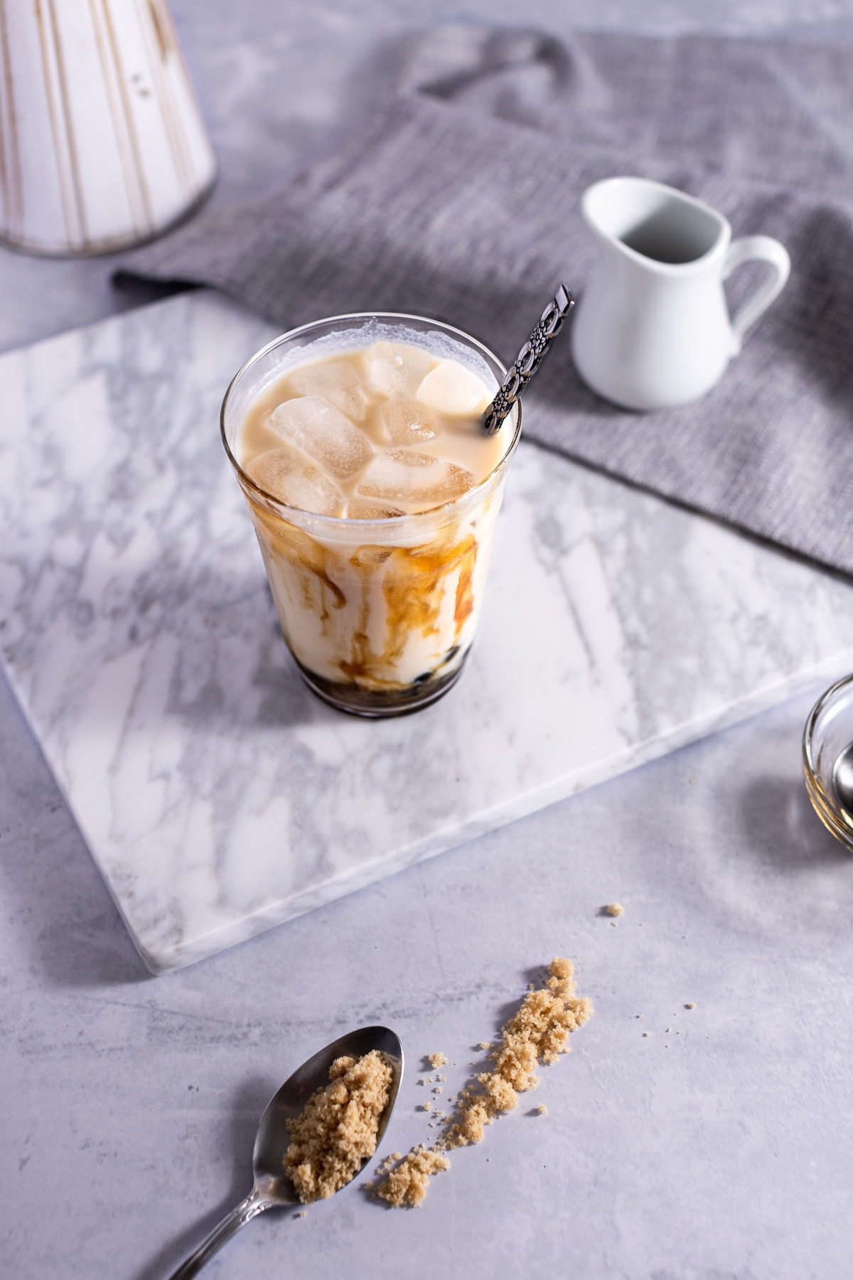 Overhead photo of tiger milk tea on grey marble board, next to a small creamer and spoon of brown sugar.