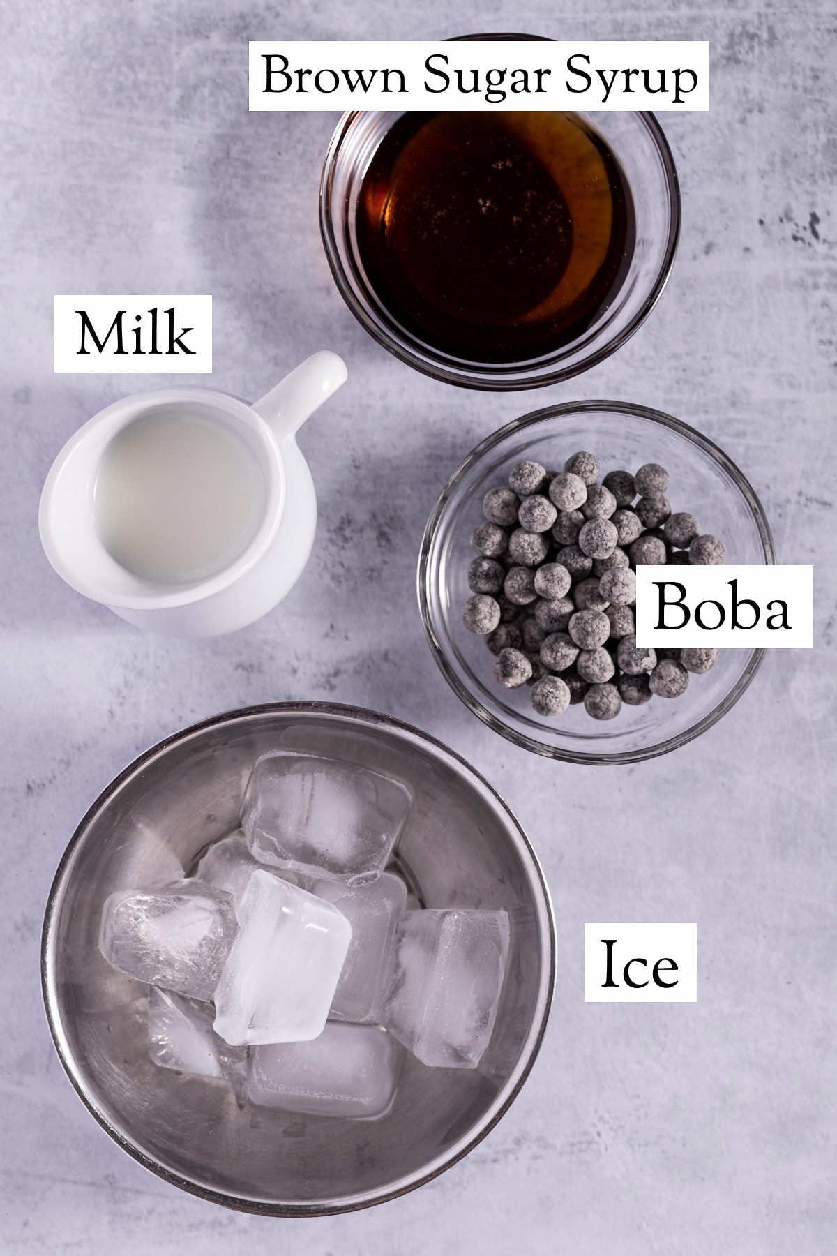 The ingredients needed to make this bubble tea recipe - ice, boba, milk, and brown sugar syrup.