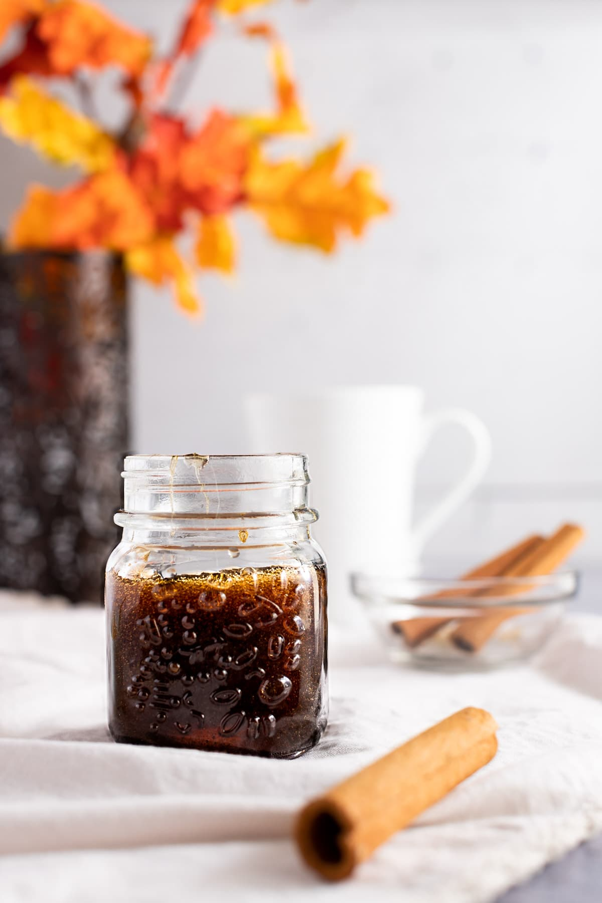 Glass jar of brown syrup, next to cinnamon sticks, with fall leaves in the background.