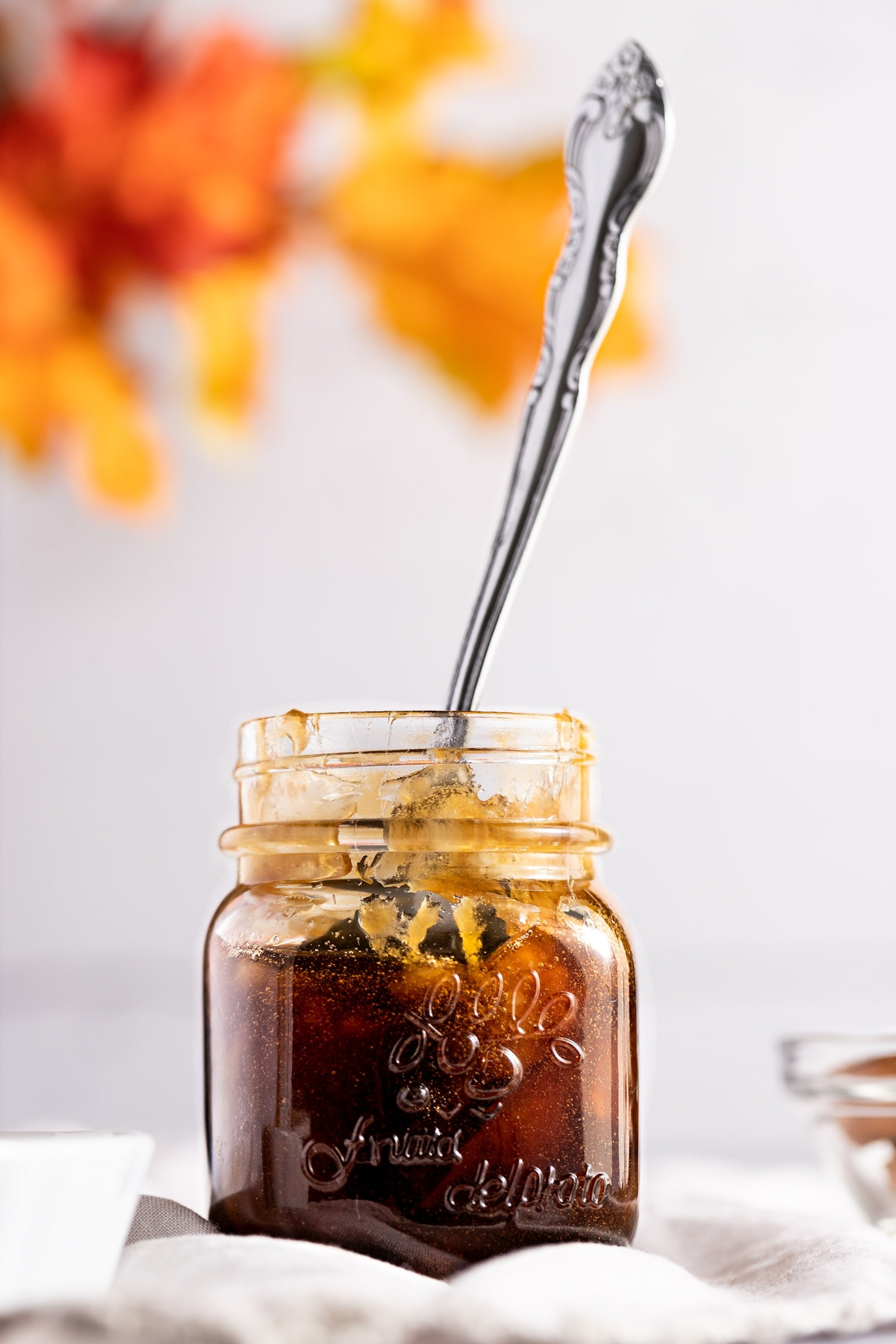 Up close photo of a small glass pot of brown sugar simple syrup, with a metal spoon sticking out of the jar, on a white background.