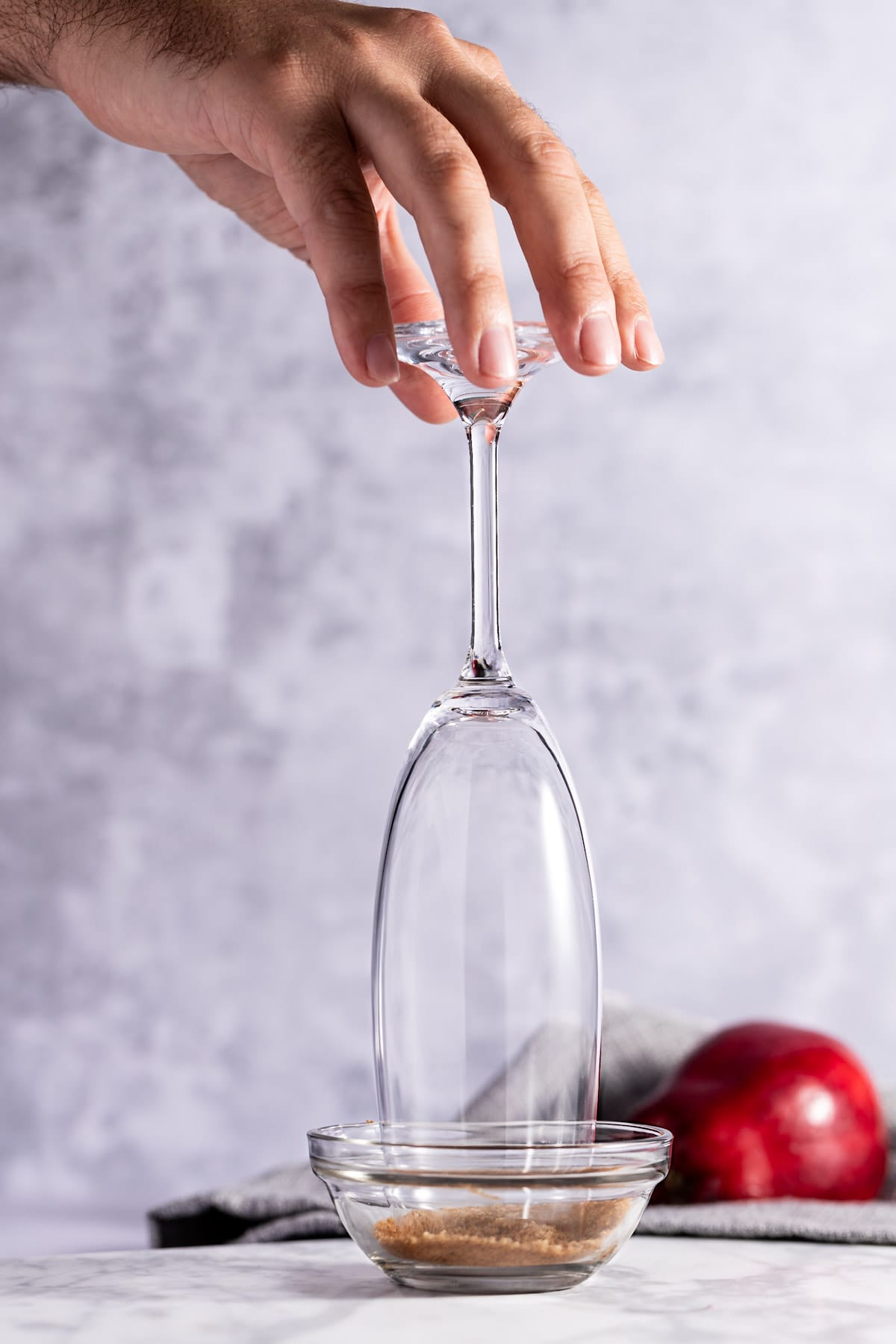 Hand holding a champagne flute and dipping it into a brown sugar and cinnamon mixture to line the rim of the glass.