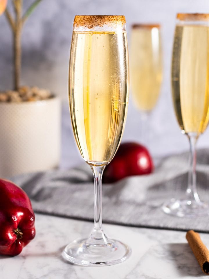 A caramel apple mimosa, on a white marble board, next to a couple fresh red apples and cinnamon sticks, on a grey background.