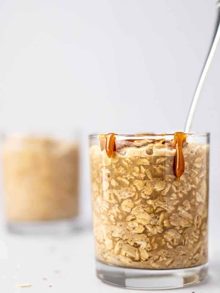 Eye level view of caramel macchiato overnight oats with caramel drizzle down the side of the glass