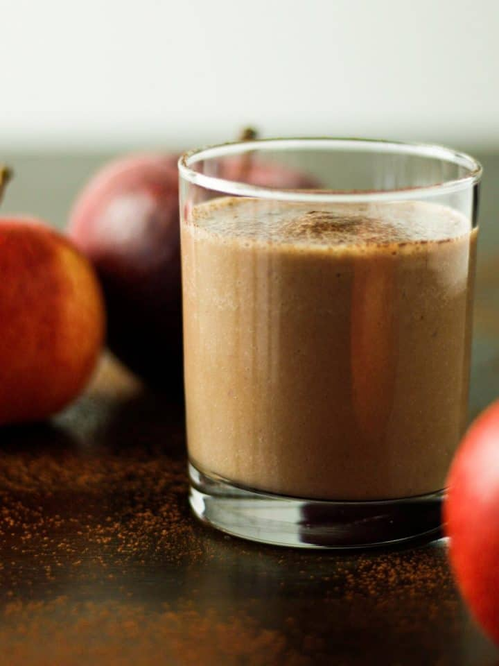 A glass of chocolate apple smoothie on the table next to three apples.