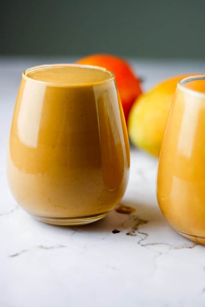 Two glasses of chocolate mango smoothie filled to the brim