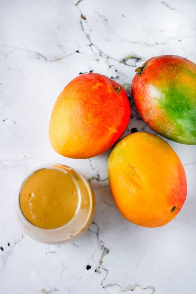 Overheard angle of a glass of chocolate mango smoothie and three ripe mangos