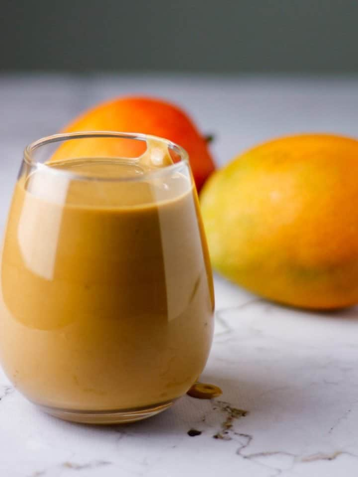 Glass of chocolate mango smoothie on table with mangoes in background