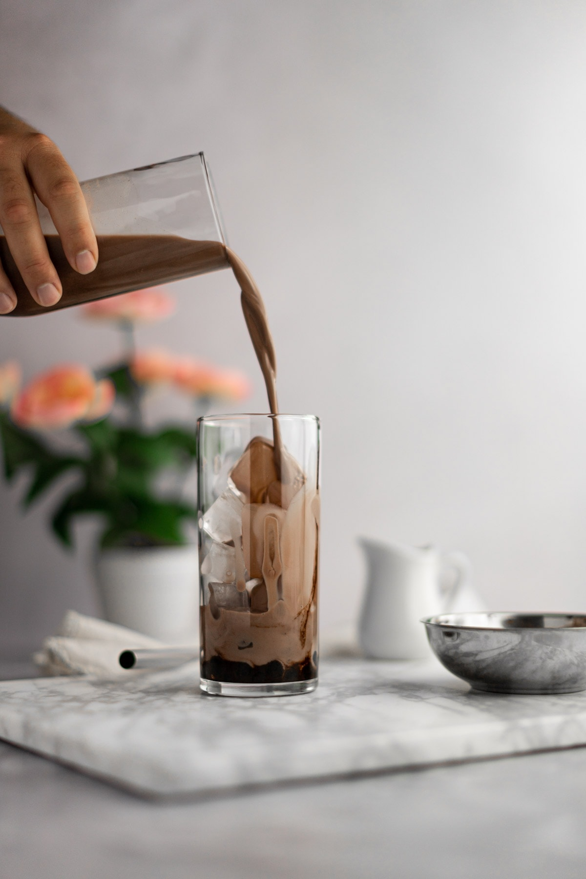 Chocolate milk tea being poured into an empty glass filled with ice and boba, on a white marble board, with pink flowers in the background.