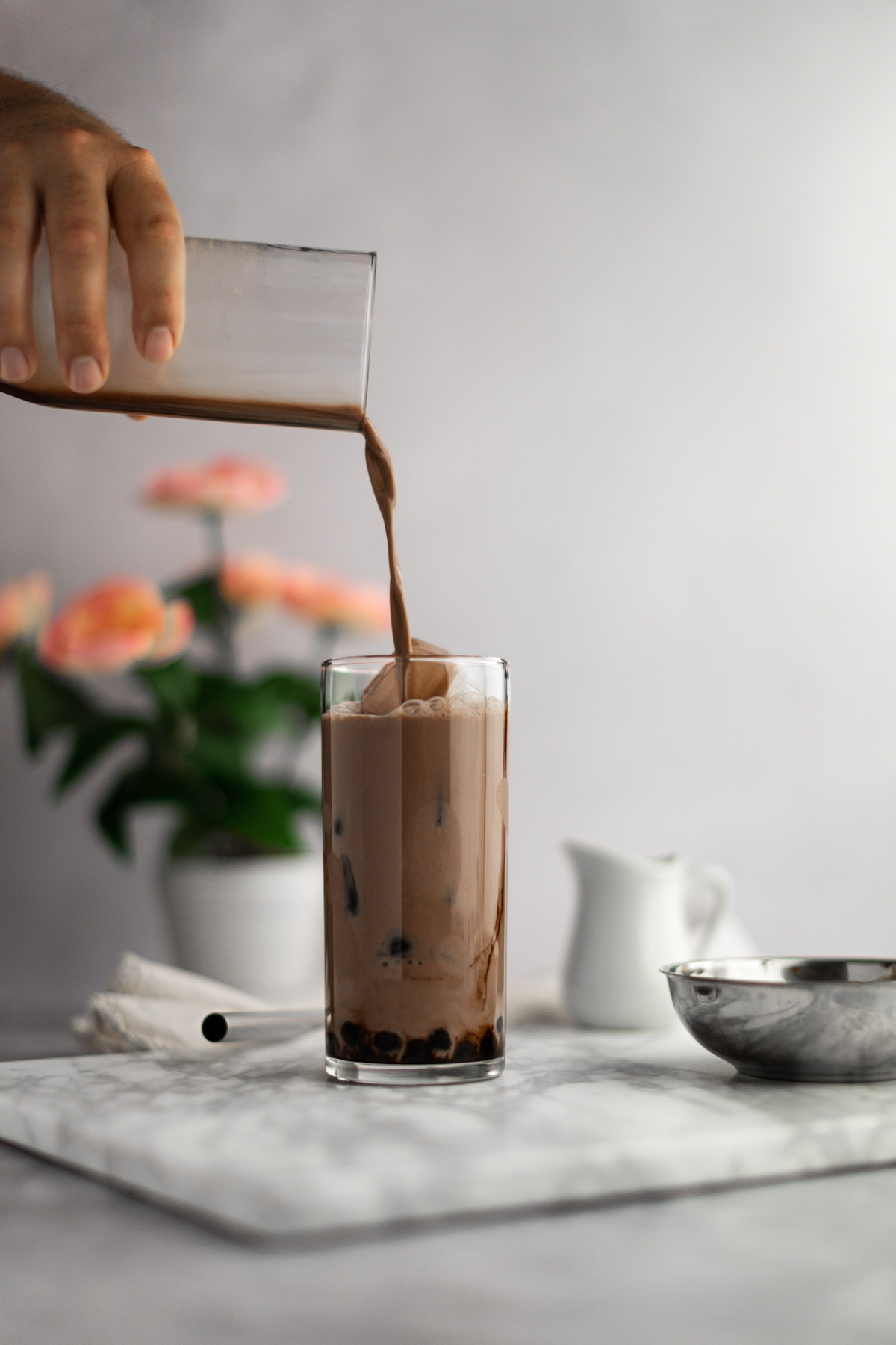 Chocolate bubble tea being poured into an almost full glass, on a grey board, with pink flowers in the background.