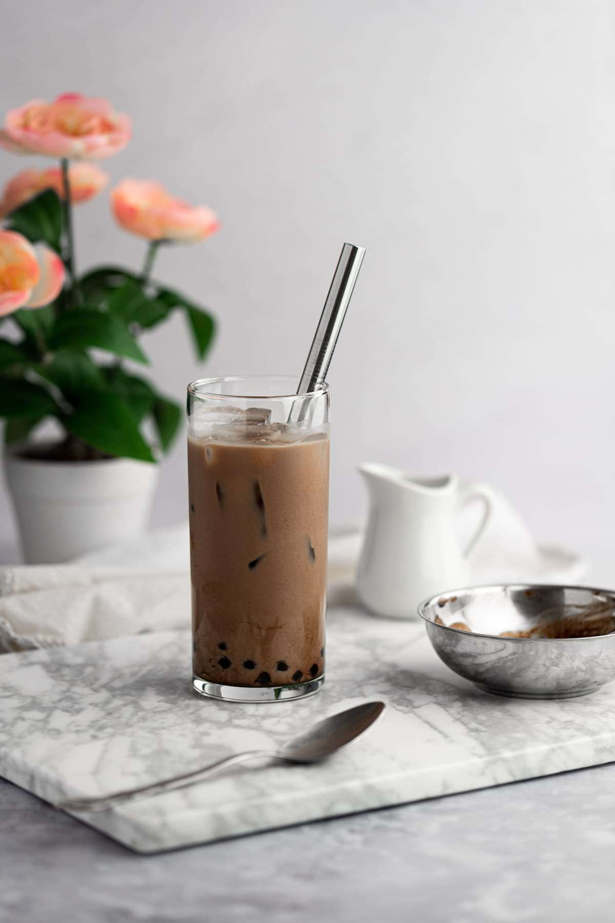 A glass of chocolate milk tea on a grey marble board, next to a metal spoon, with a flower pot in the background.