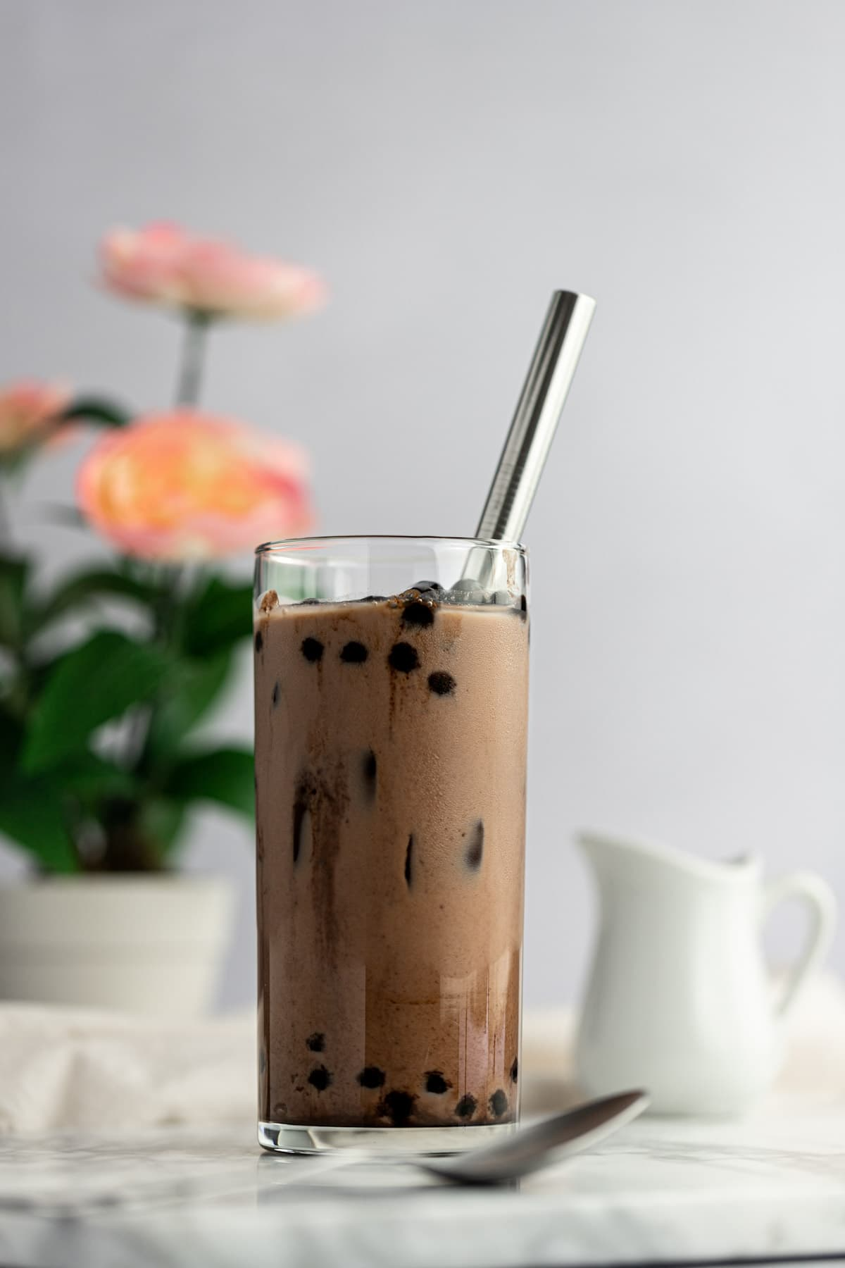 Up close photo of a glass of chocolate milk tea, filled with ice and boba, with a spoon in front of the glass, and a small creamer behind, on a white background.