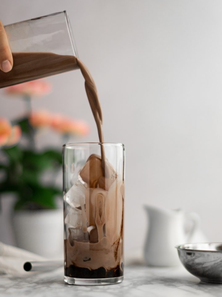 Chocolate milk tea being poured into a glass filled with chocolate soaked boba and ice, pink flowers in the background in front of a white wall.