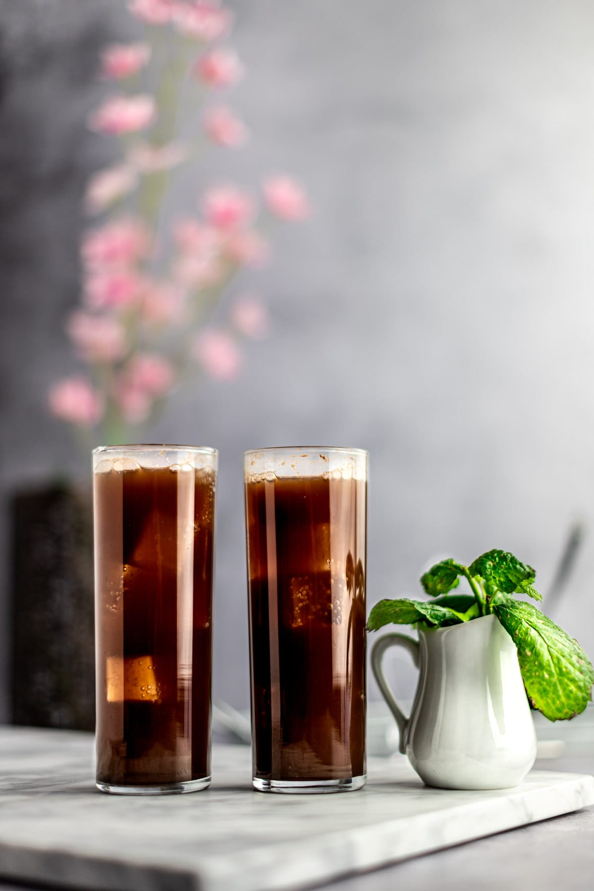 Two chocolate mojitos lined up side by side on a white marble board, next to a small white jug filled with fresh mint leaves.