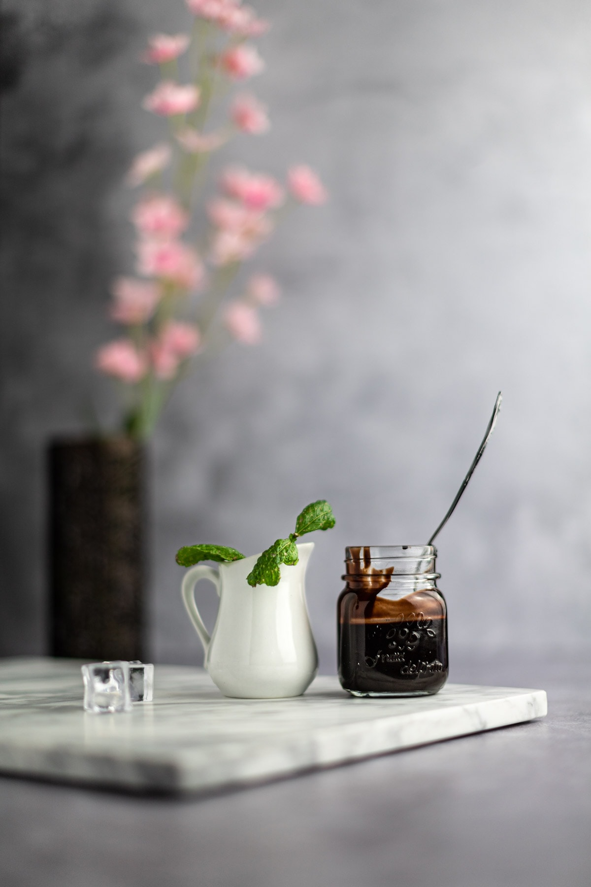 A small white jar filled with mint leaves sitting next to a mason jar filled halfway with chocolate syrup and a spoon sitting in the jar, pink flowers in the background.