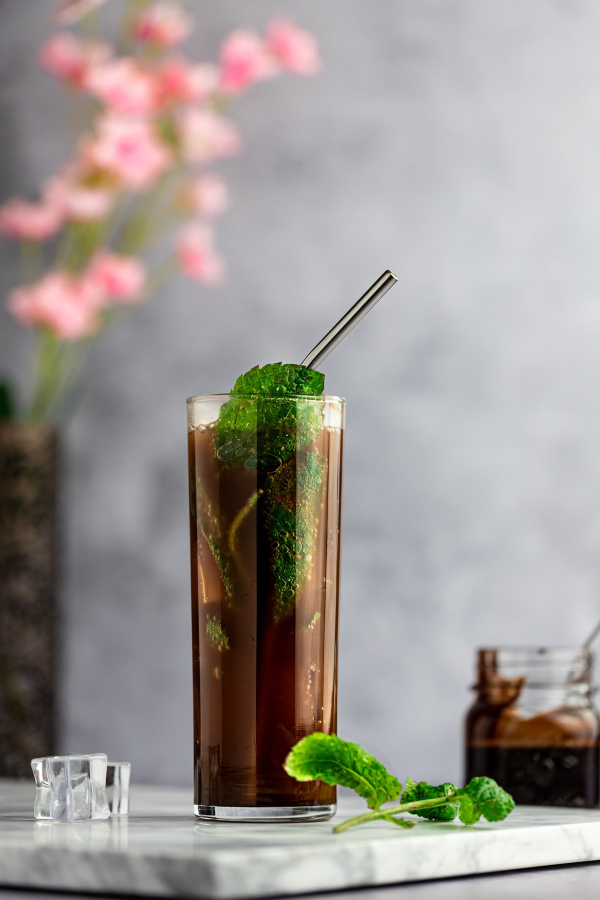 Up close photo of a chocolate mojito, with a metal straw and garnished with fresh mint leaves, on a marble board, next to mint leaves and ice cubes, with pink flowers behind.
