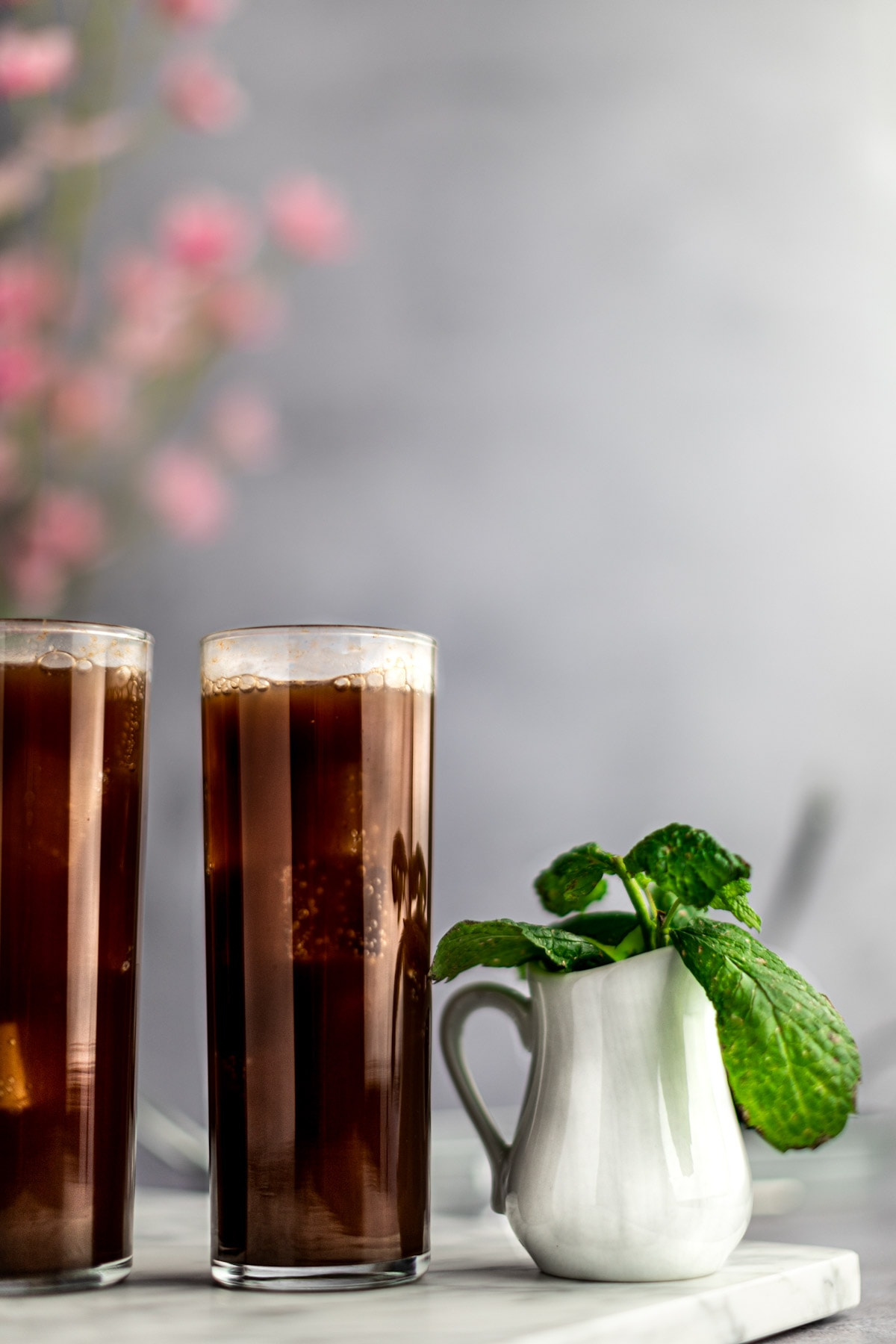 Two glasses of chocolate mojito and a white jar filled with fresh mint lined up beside each other, on a marble board, with flowers in the background.