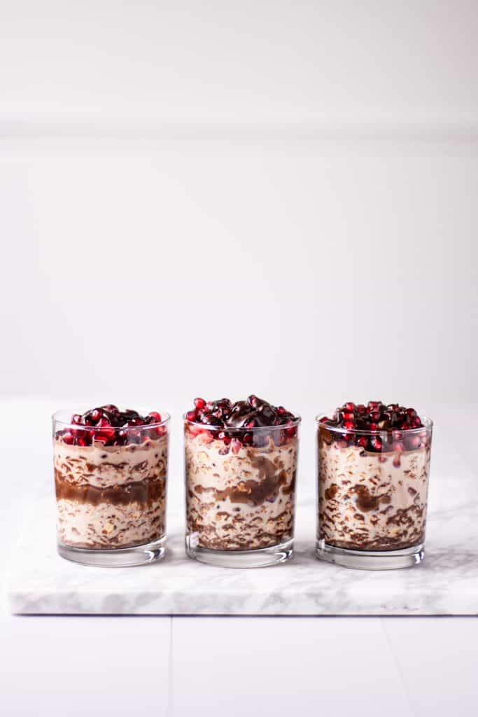 Three containers of chocolate pomegranate overnight oats sitting in a row on a white marble serving board