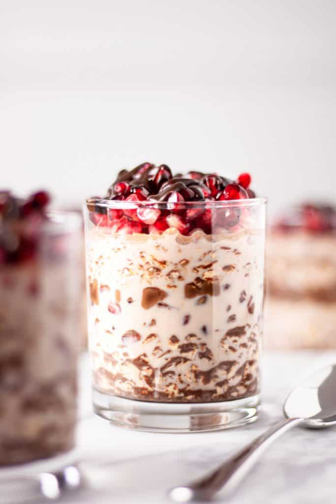 A glass of chocolate pomegranate overnight oats on a white table with other jars of overnight oats and a spoon around surrounding it