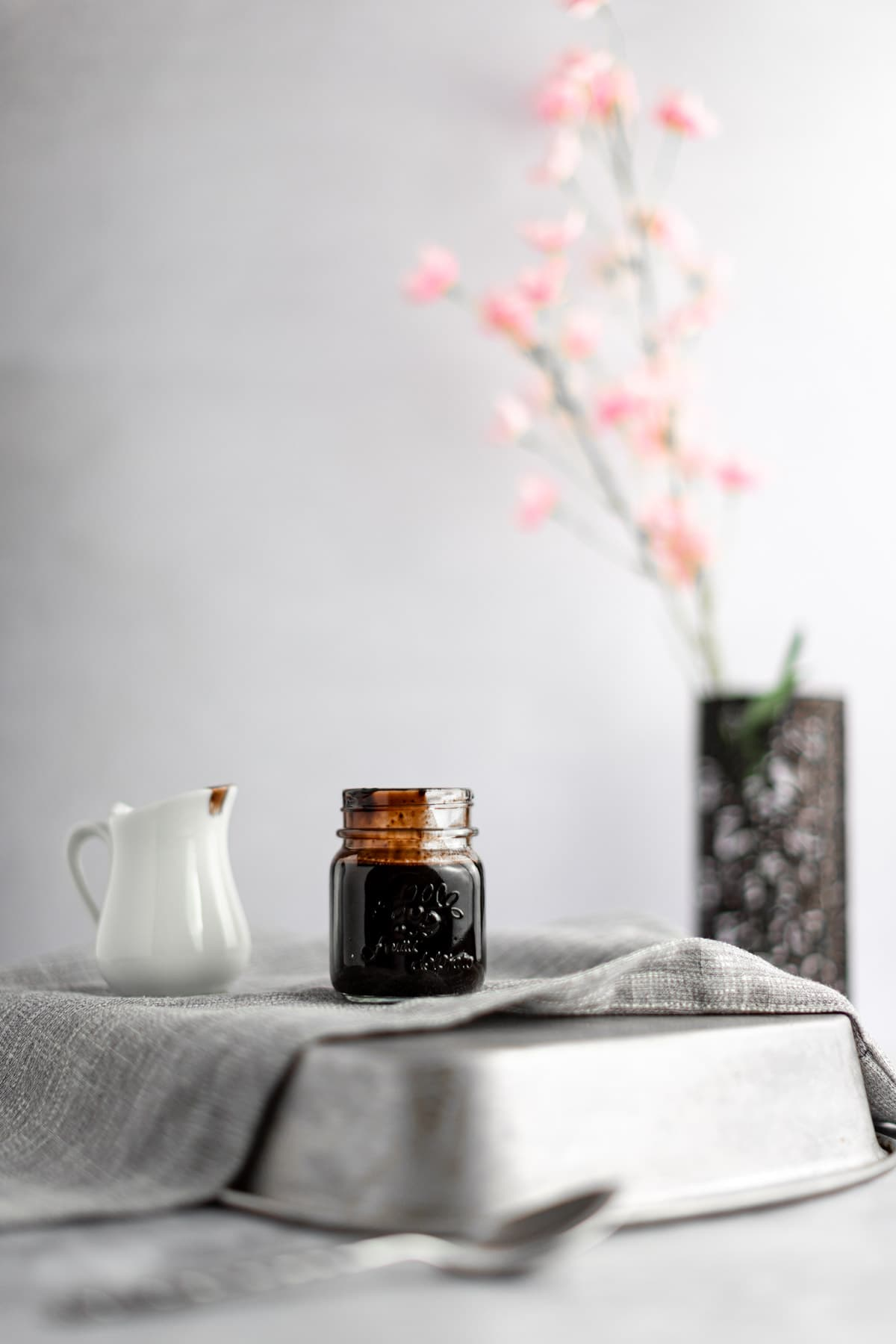 A small glass jar of syrup sitting on a grey napkin on a flipped over tin pan, next to a creamer just, with pink flowers in the background.