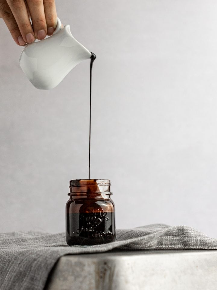 Chocolate simple syrup being poured into a small glass jar, sitting on a grey napkin on a reversed metal tin pan.