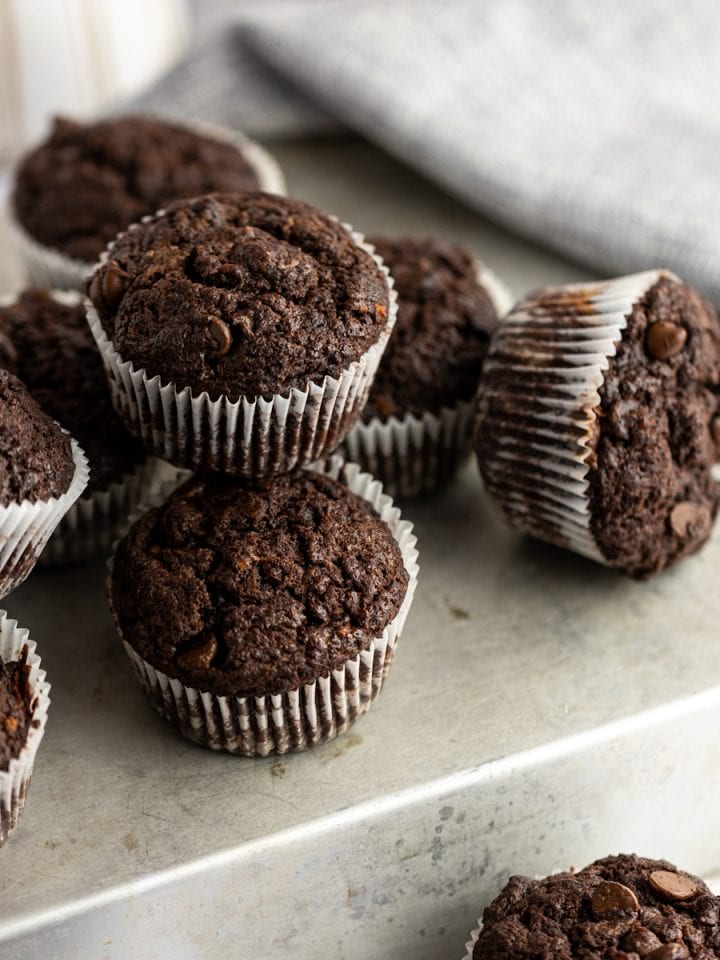 Overhead photo of chocolate sweet potato muffins in a pile on top of a flipped over baking tray, with a grey napkin in the background.