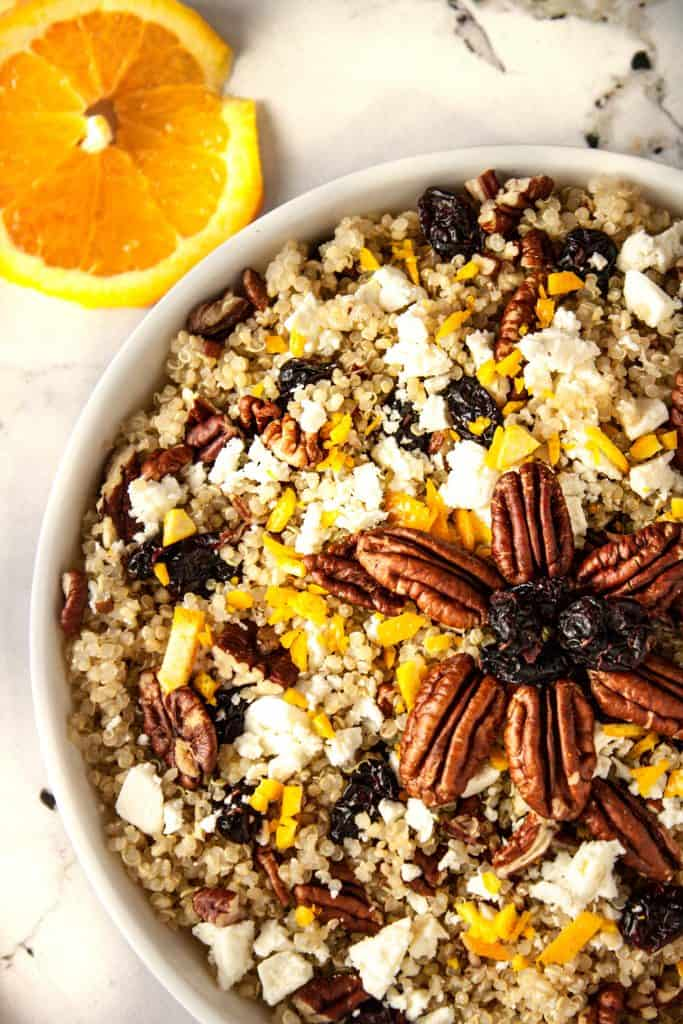 Up close overhead view of a bowl of cranberry pecan quinoa salad on a white marble table next to orange slices