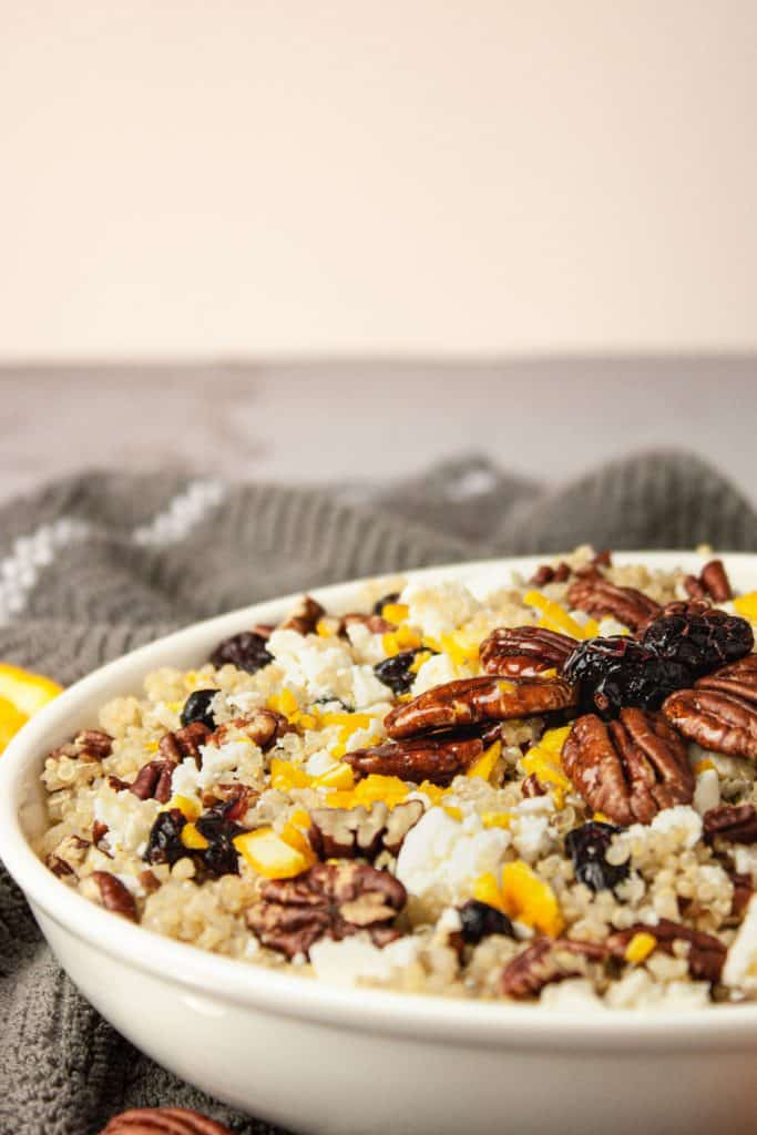 Side view of a white bowl of cranberry pecan quinoa salad on a grey hand towel