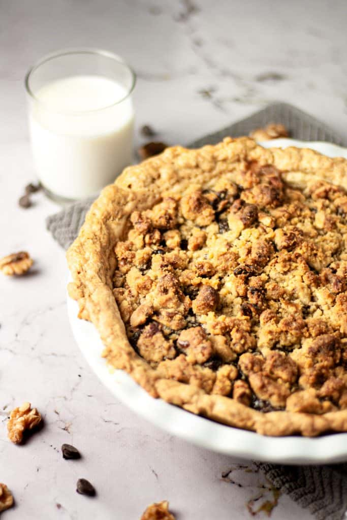 Up close view of a fresh out of the oven pear chocolate pie, with a glass of milk, walnuts and dark chocolate chips in the background