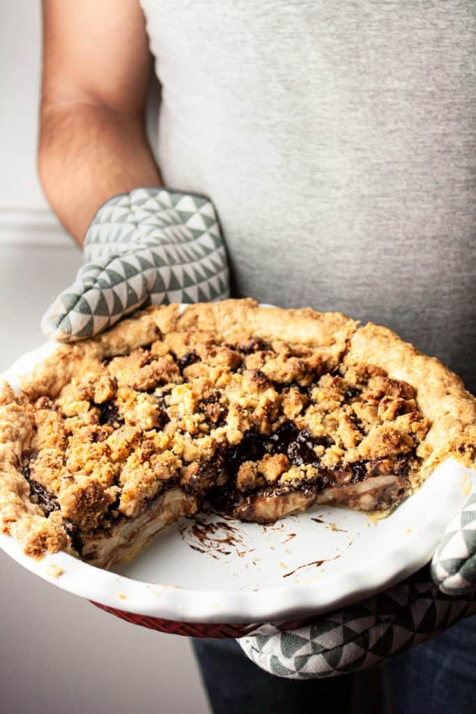 Up close view of a man holding a partially eaten pear chocolate pie with checkered oven mitts