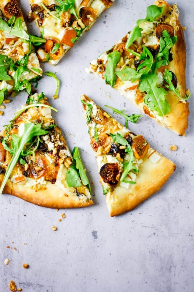 sliced fig, pear, walnut, brie, honey and goat cheese pizza with slices spread out