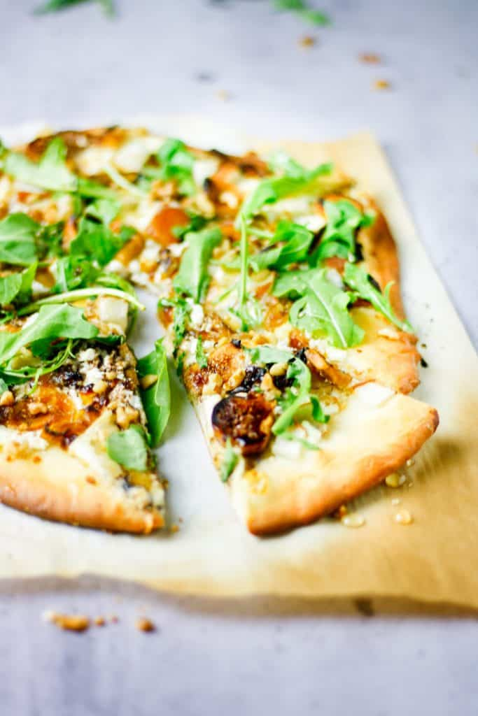 sliced fig, pear, walnut, brie, honey and goat cheese pizza with one slice pulled away