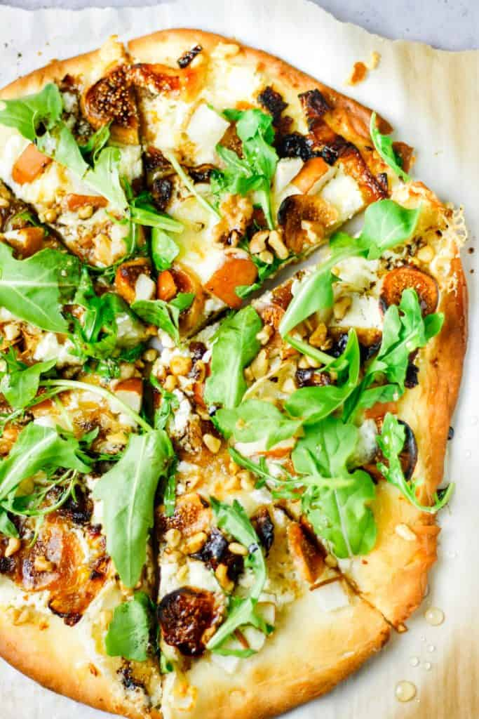 overhead view of whole fig, pear, walnut, brie, honey and goat cheese pizza cut into slices