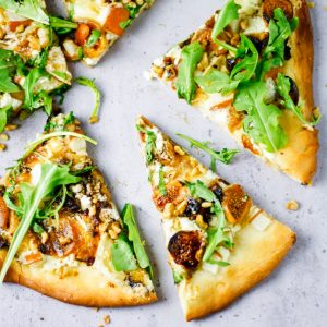 Fig, pear, walnut, brie, honey and goat cheese pizza slices spread out on table