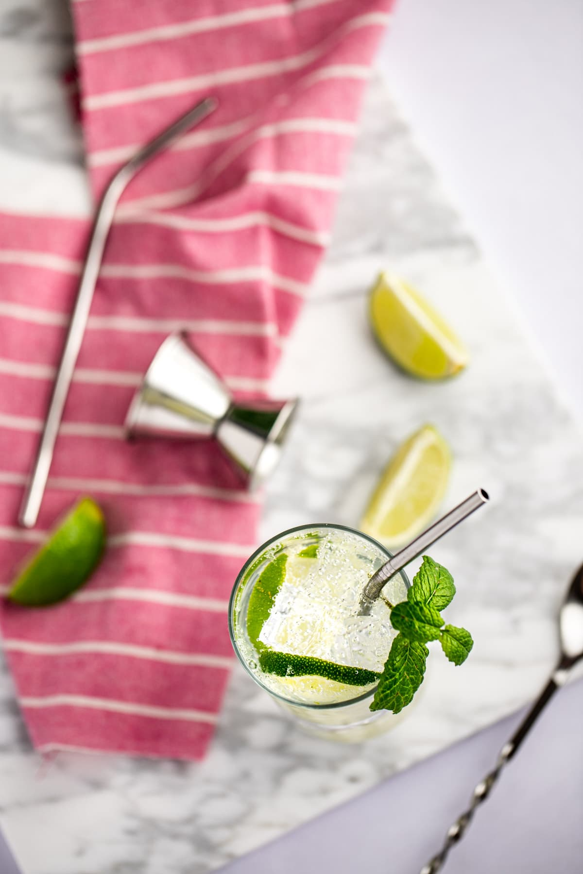 Overhead photo of a mojito, garnished with mint, on a white marble board, next to a pink napkin, lime slices and a metal straw.