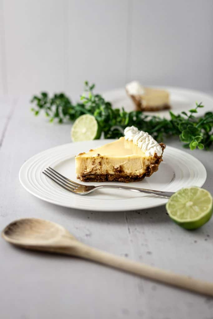Side angle view of a slice of pie on a white plate next to a fork, with lime halves, a wooden spoon and green garland in the background