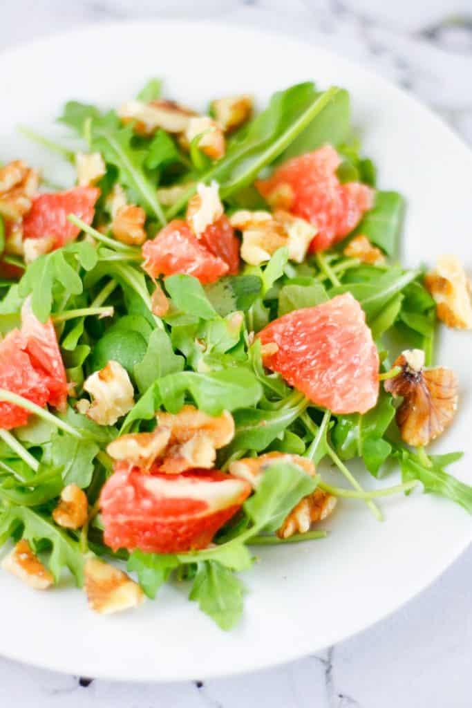 Up close view of a bowl of grapefruit arugula salad with walnuts.