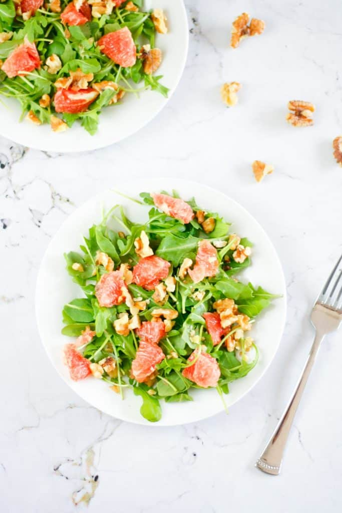 Overhead view of a plate of grapefruit arugula salad on a marble table with a fork on the side.