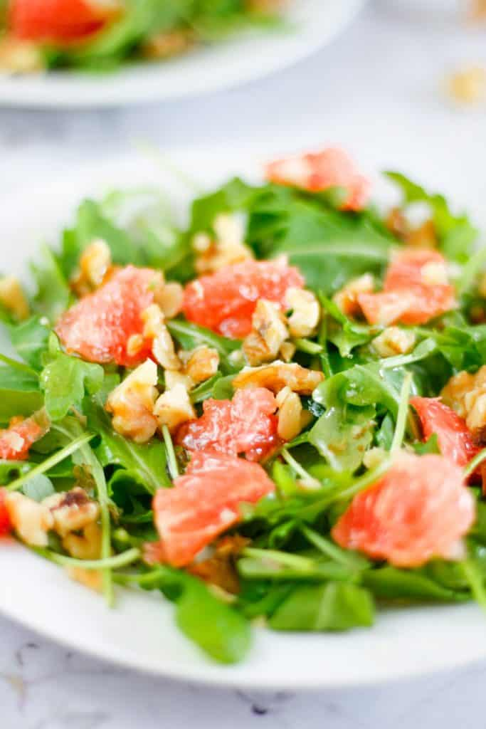 Up close side view of a plate of grapefruit arugula salad