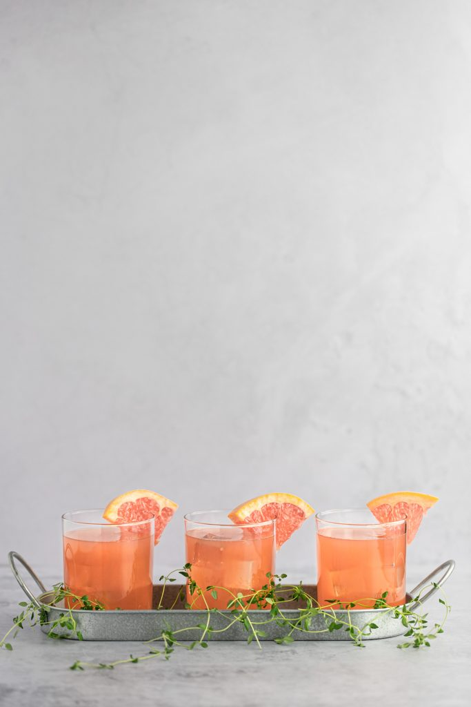 Three grapefruit cocktails beside each other in a metal tray, with fresh thyme scattered at the bottom.