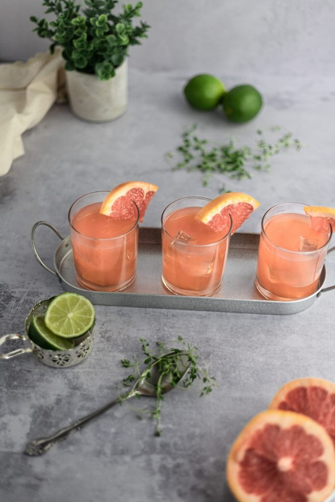 Overhead shot of three crush cocktails on a metal tray, slices of grapefruit and lime and a spoonful of thyme scattered around them.
