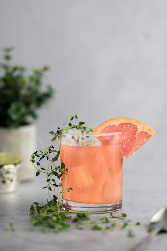 An individual cocktail with a grapefruit slice on the rim and fresh thyme along the side of the glass.