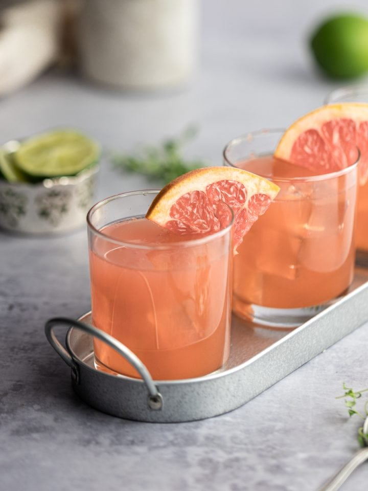 Three grapefruit crush cocktails on a metal serving tray, garnished with grapefruit, limes in the background.