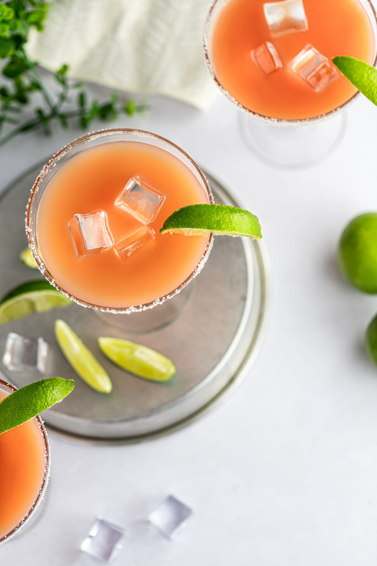 Overhead photo of three margaritas, with salt around the rims of the glass and each drink garnished with a lime slice.