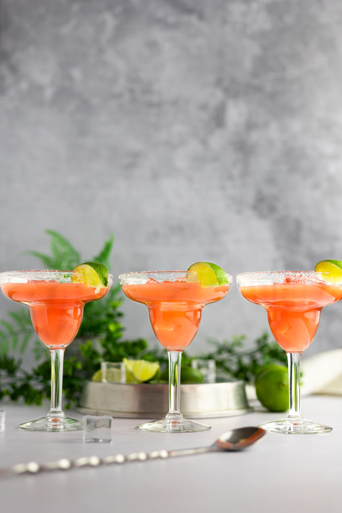 Three guava margaritas in a line, each garnished with a slice of lime, a metal spoon in the foreground and limed and green leaves in the background.