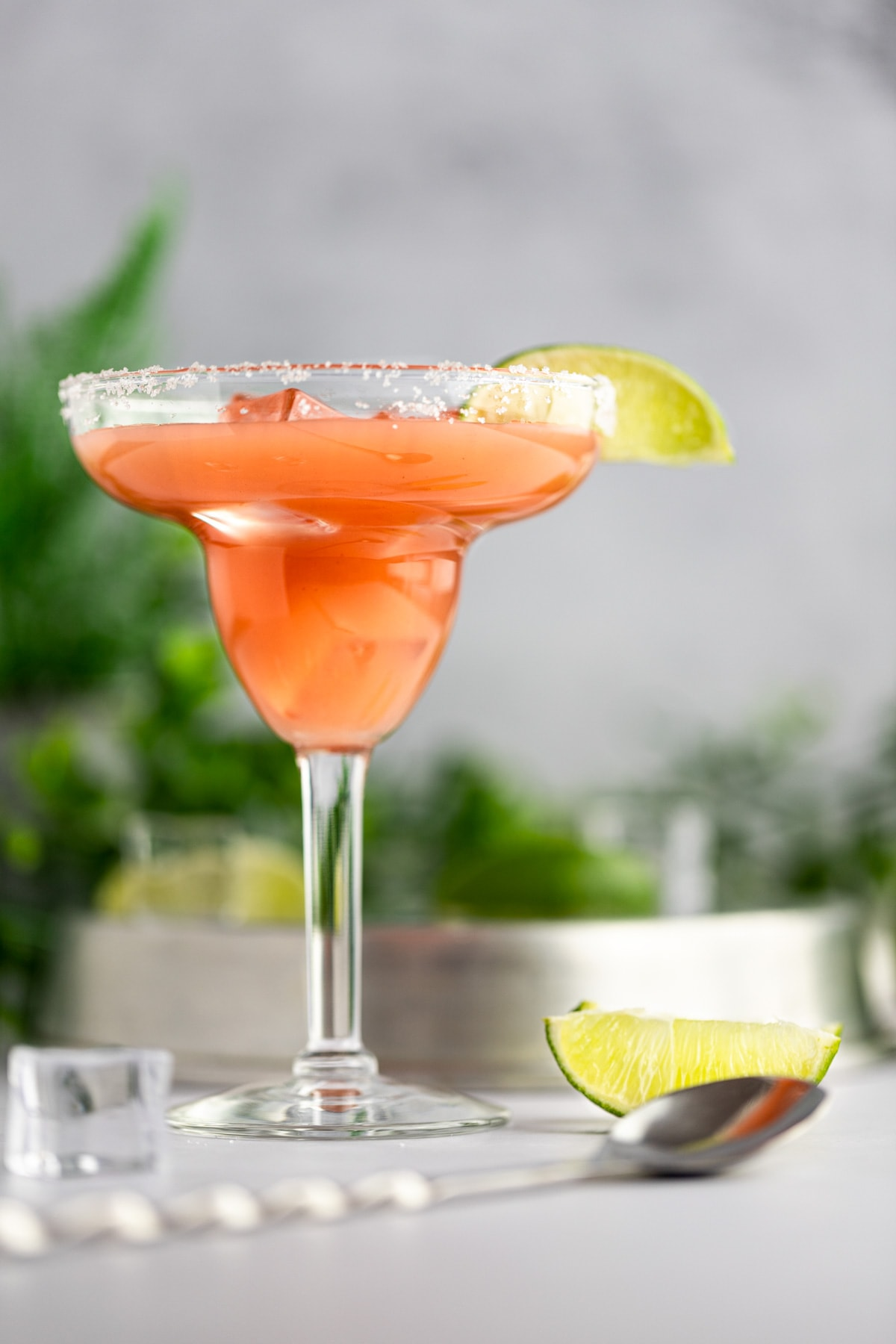 Up close view of a guavarita, next to a slice of lime and ice cubes, with green plants in the background.