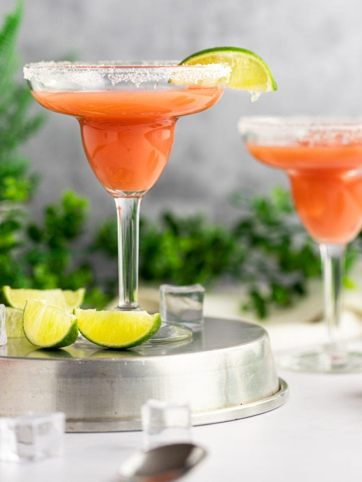 A couple guava margaritas with a slice of lime and salt around the edge of the glass, standing on a metal tin, with green leaves in the background.