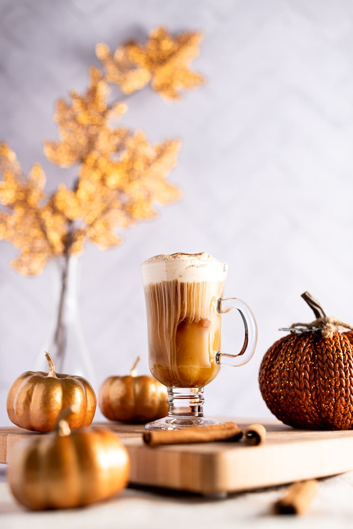 Iced chai latte with pumpkin cold foam on a wooden board, surrounded by decorative pumpkins, and golden leaves in the background.